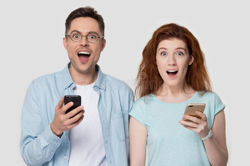 Excited millennial couple hold cellphones happy reading good news. Surprised young couple stand isolated on grey studio background hold smartphones happy win stock photo