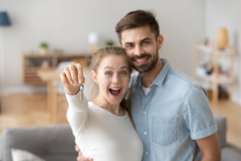 Excited millennial couple holding key to new house. Portrait of happy millennial couple hug holding key to own apartment, young husband and wife excited to buy stock photography