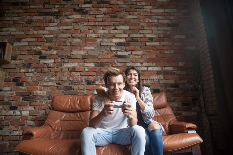 Happy millennial couple playing video games at home royalty free stock photo
