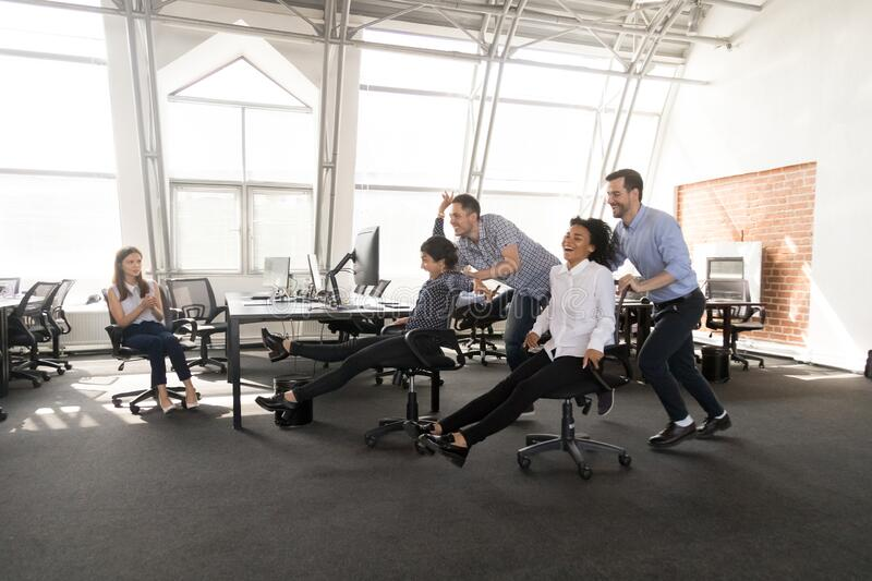 Excited diverse workers have fun racing on chairs in office royalty free stock photography