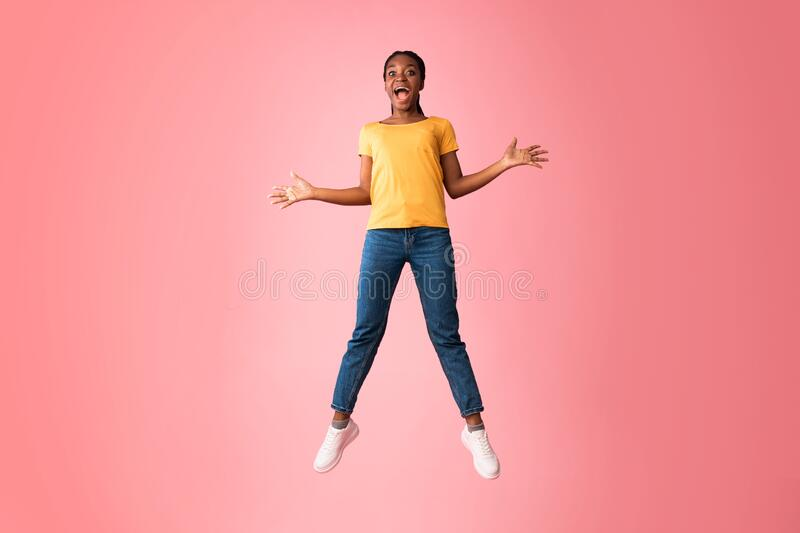 Excited Millennial Girl Jumping And Shouting Over Pink Background. Excited African Millennial Girl Jumping And Shouting In Joy Over Pink Background. Studio Shot stock image