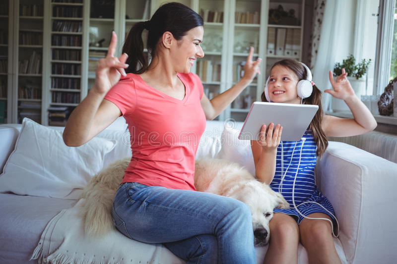 Excited mother and daughter using digital tablet and dancing stock image
