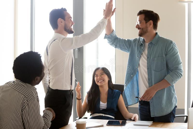 Excited motivated male team people give high five at meeting. Excited motivated male team people give high five at diverse group meeting celebrate shared win royalty free stock photos