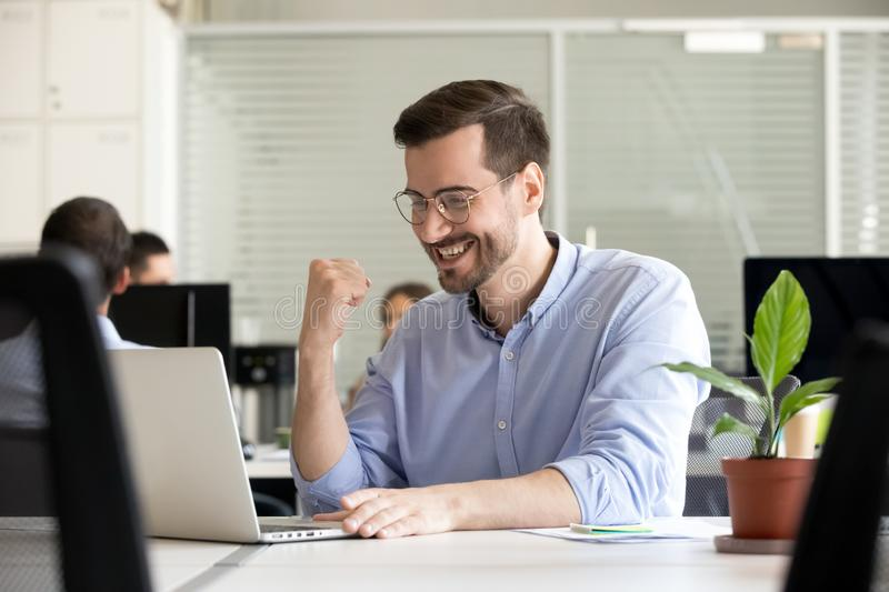 Excited motivated worker happy by receiving good news in email. Excited motivated male worker happy by receiving good news in email looking at laptop, lucky royalty free stock images