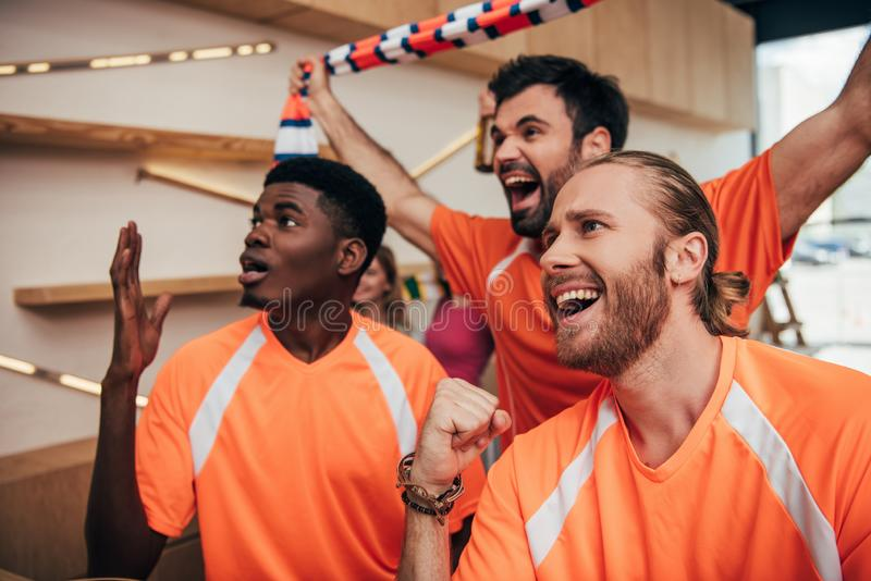 excited multicultural male football fans in orange t-shirts celebrating and gesturing during watch of soccer match royalty free stock images