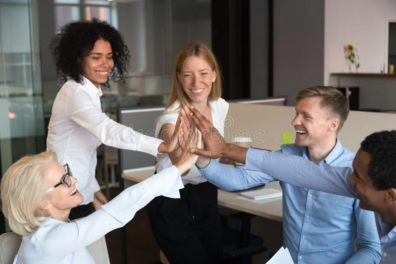 Excited diverse colleagues join hands showing unity at meeting. Excited multiracial colleagues give high five engaged in teambuilding at informal group meeting royalty free stock photos