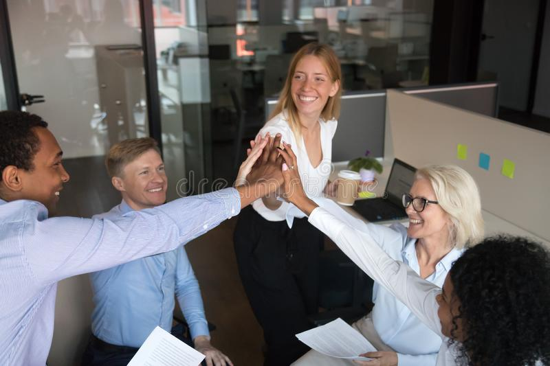 Excited multiracial employees giving high five at briefing, staff training royalty free stock photos