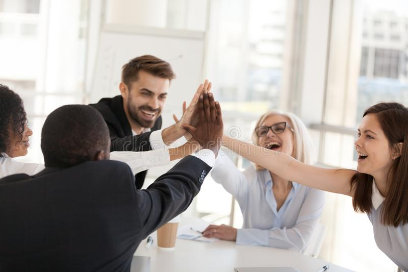 Excited multiracial office associates employees group giving hig royalty free stock images