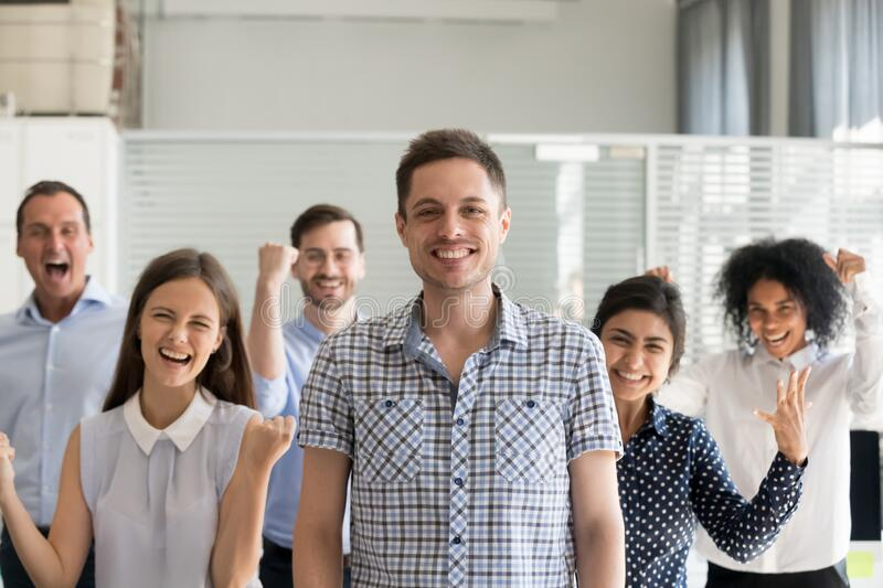 Excited multiracial team posing together with male team leader stock images