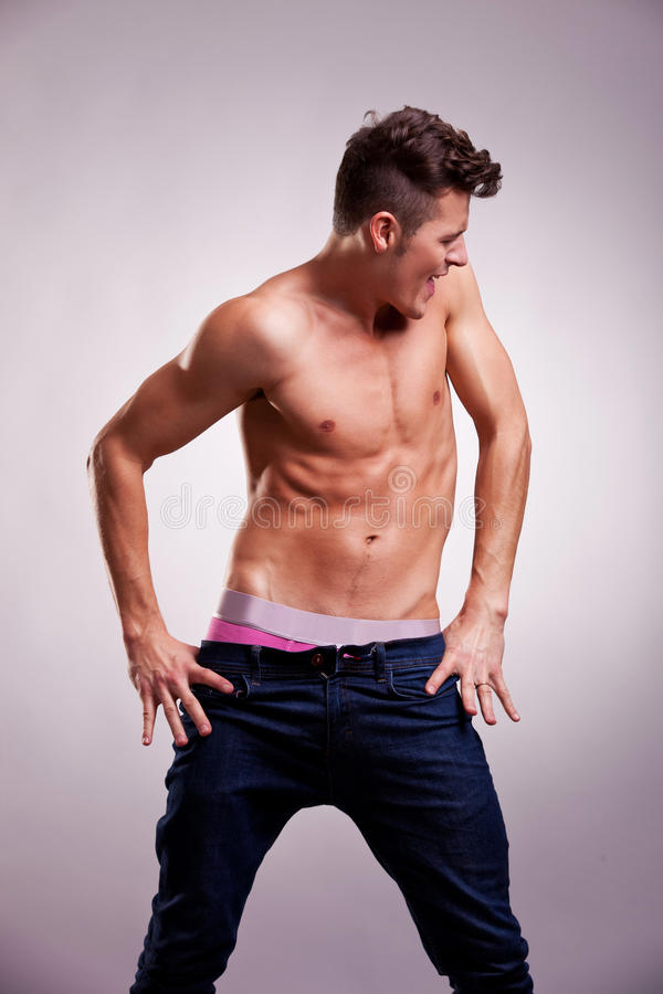 Excited muscular fashion model in a dance pose royalty free stock photo