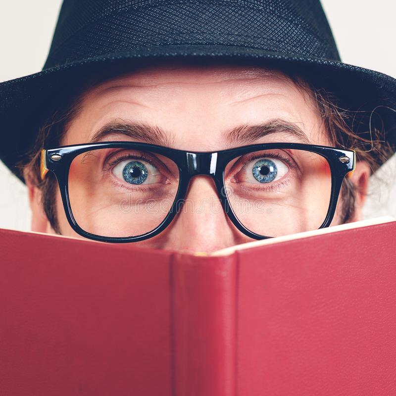Excited nerd hiding behind books. Playful happy young man in funny glasses and vintage hat holding a book. Nerd hipster guy in hat stock photography