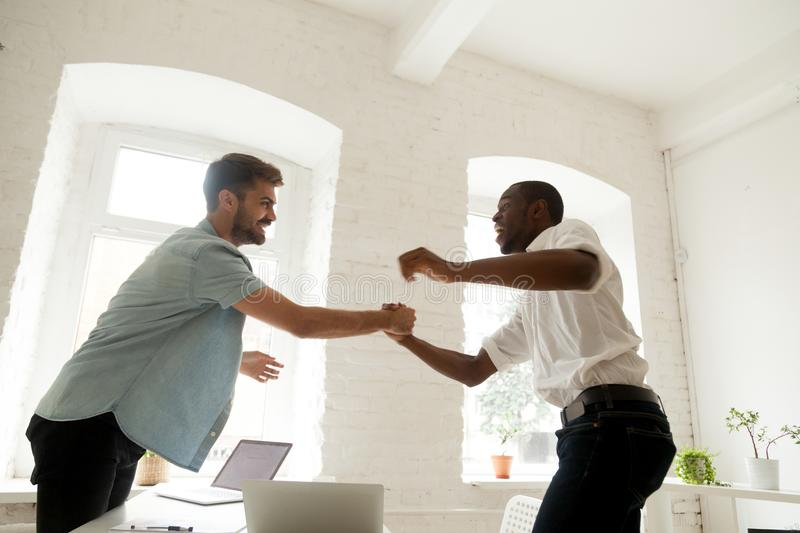 Excited office workers handshaking celebrating business success. Two excited funny diverse office workers handshaking celebrating shared business success royalty free stock photo
