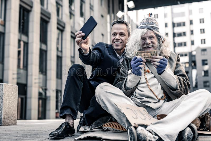 Vain rich man in costume making selfie of donation money royalty free stock images