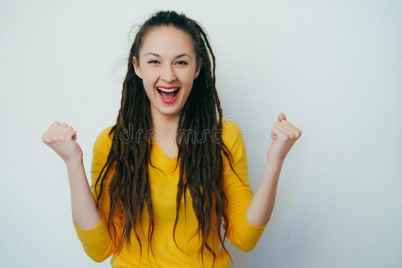 Excited overjoyed Beautiful girl with dreadlocks and in a yellow bright sweater feel happy looking at camera, euphoric girl winner stock photography