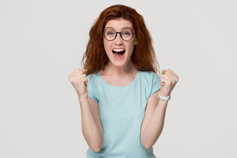 Excited overjoyed young redhead woman feel happy looking at camera stock image