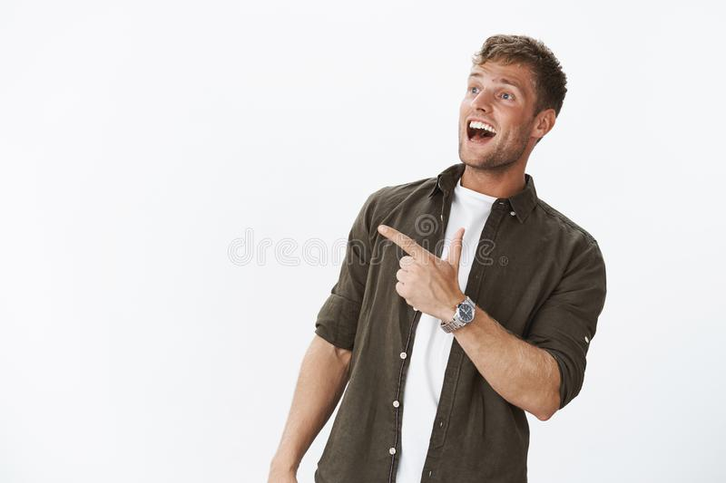 Excited overwhelmed joyful friendly-looking masculine guy with fair hair, blue eyes and white smile pointing, looking. Left impressed and fascinated with cool royalty free stock photography