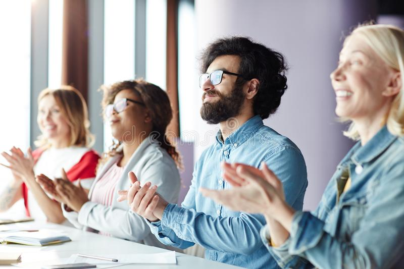 Excited people applauding speaker at business forum stock image
