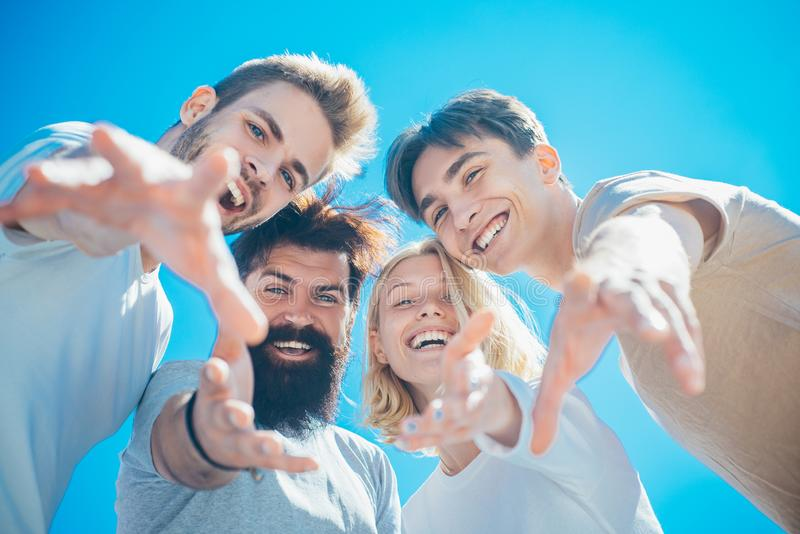 Excited people. Group of happy cheerful smiling friends offer their hands down to the camera at clear blue sky stock images