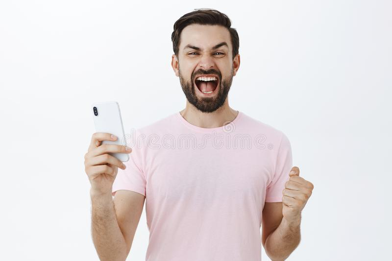 Excited and pleased triumphing adult bearded man yelling yeah clenching fists in victory and success as winning in stock photos