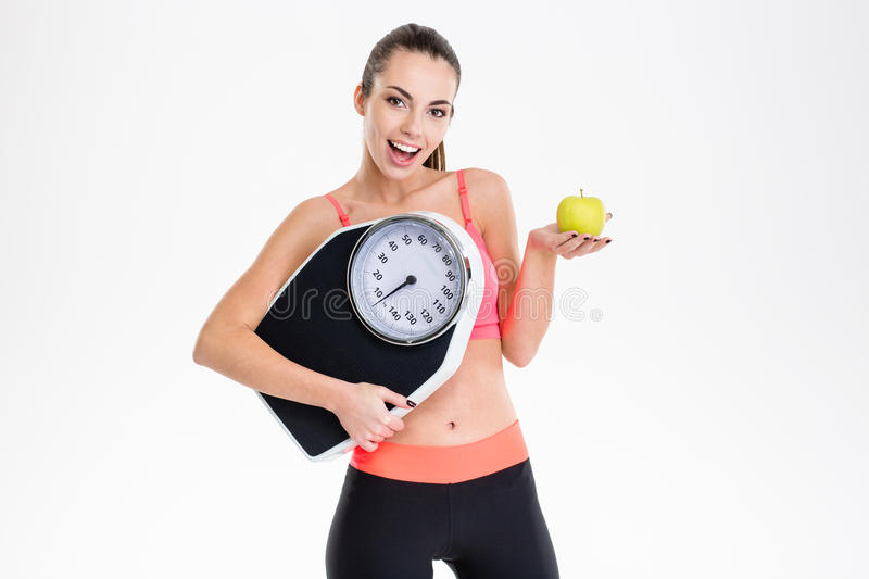 Excited positive fitness girl holding weighing scale and apple. Excited positive fitness girl in tracksuit holding weighing scale and apple over white background royalty free stock photography
