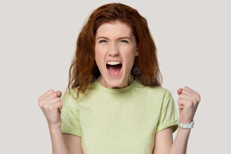 Excited red-haired girl scream with happiness about success stock images