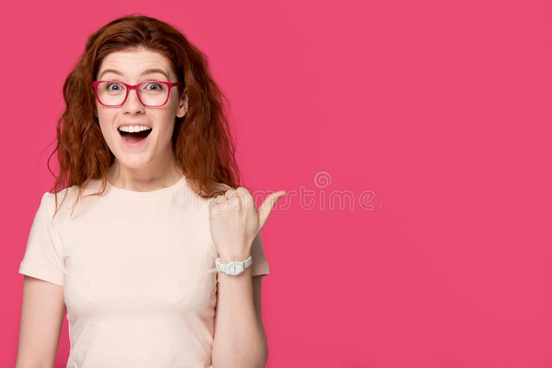 Excited redhead girl student in glasses advertising great sale offer stock photography