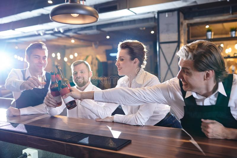 Excited restaurant colleagues clinking beer bottles at bar count royalty free stock images
