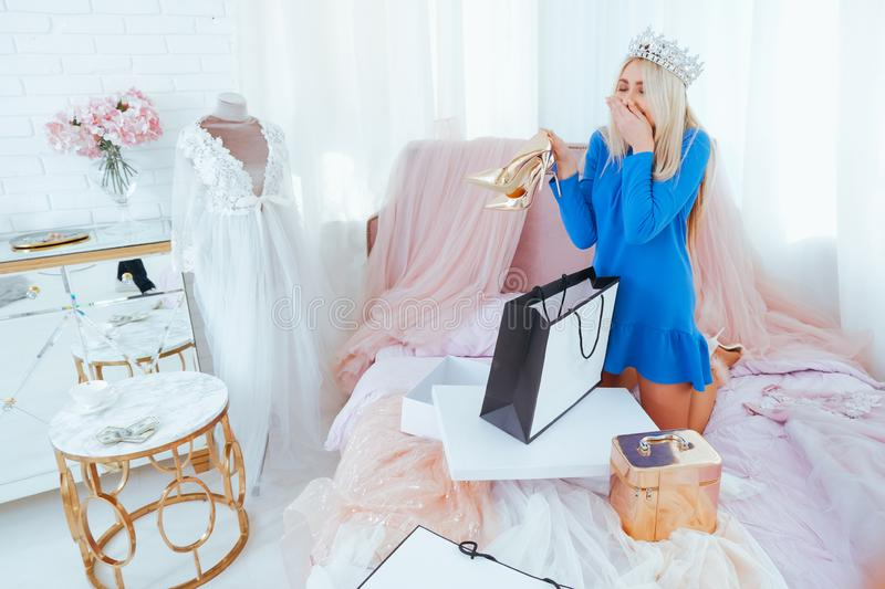 Excited rich girl shopping flamboyant bedroom. Excited rich girl after shopping in flamboyant bedroom. Blonde lady in tiara on bed unpacking dresses and heeled stock photography