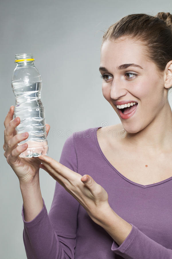 Excited 20s girl showing bottle of fresh zesty water. Thrilled young beautiful woman wearing purple shirt showing bottle of citrus mineral water royalty free stock images
