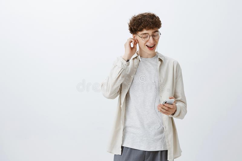 Excited and satisfied young good-looking hipster guy in round glasses with curly hair putting on earphone listening cool royalty free stock photo
