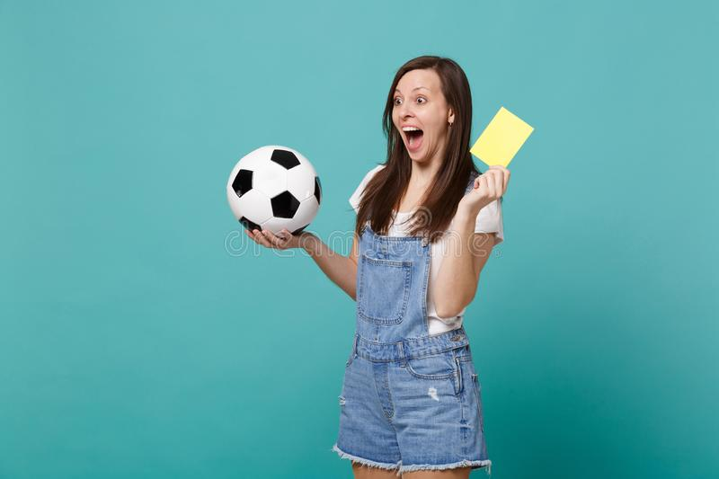 Excited screaming woman football fan support team with soccer ball, yellow card, propose player retire from field. Isolated on blue turquoise background. People royalty free stock photo