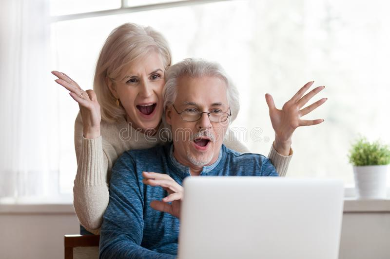 Excited senior couple looking at laptop surprised by good news royalty free stock images