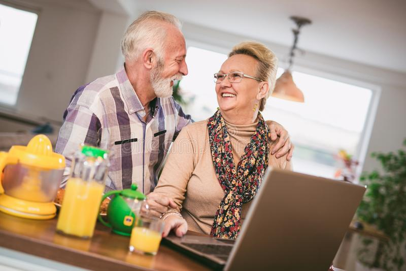 Excited senior couple looking at a laptop together stock photo