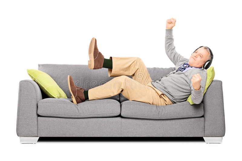 Download Excited Senior Male Seated On A Sofa Listening Music Stock Photo - Image: 35250792