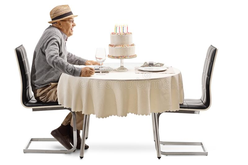 Excited senior man with a birthday cake at a restaurant table. Isolated on white background royalty free stock photography