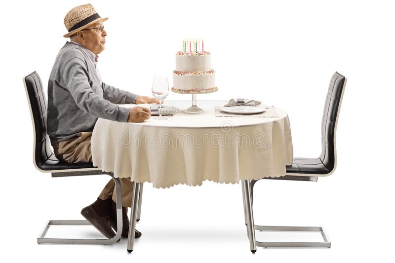 Excited senior man blowing candles on a cake at a restaurant table royalty free stock image