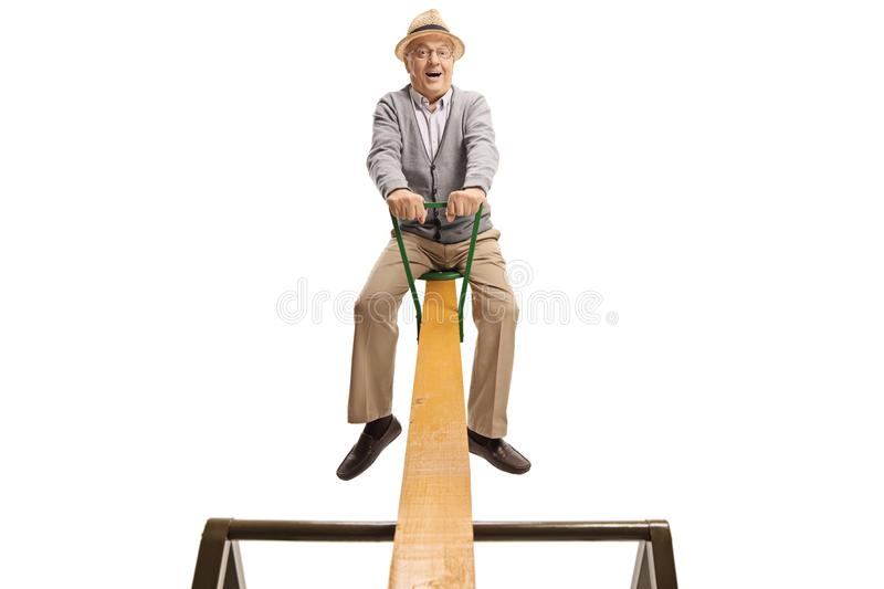 Excited senior man on a seesaw royalty free stock image
