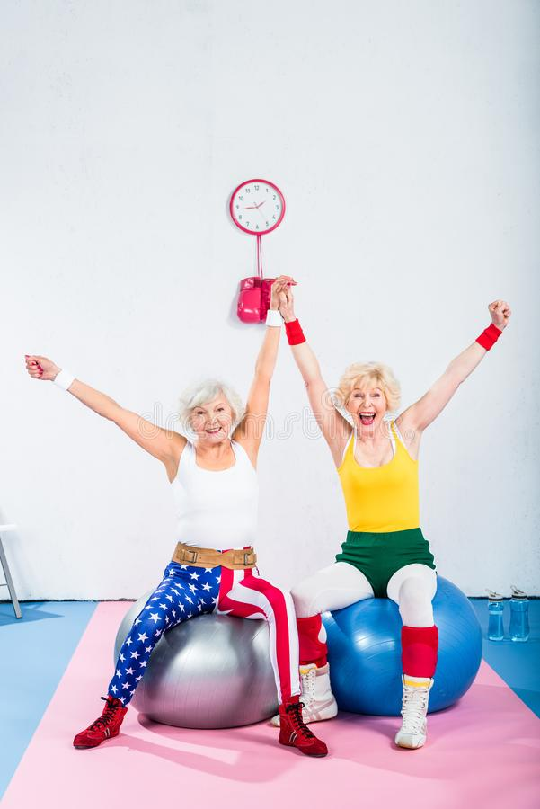 excited senior sportswomen sitting on fitness balls and smiling royalty free stock images