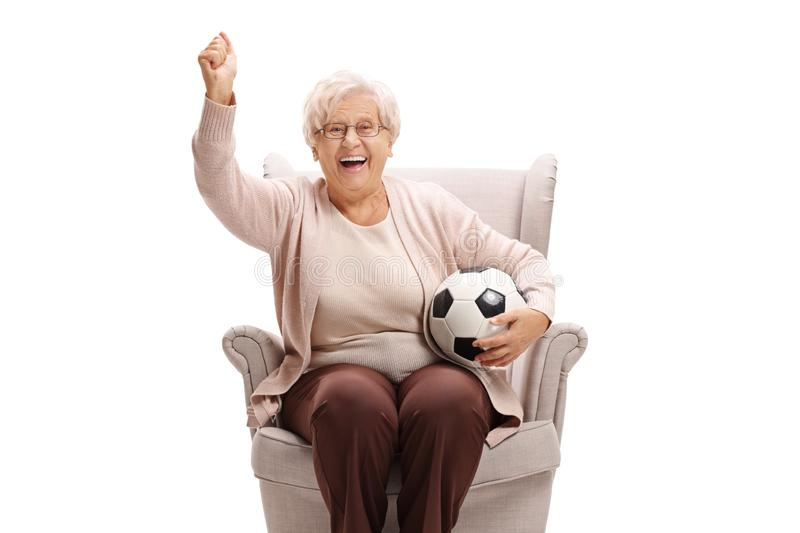 Excited senior woman with a football sitting in an armchair and cheering royalty free stock photo