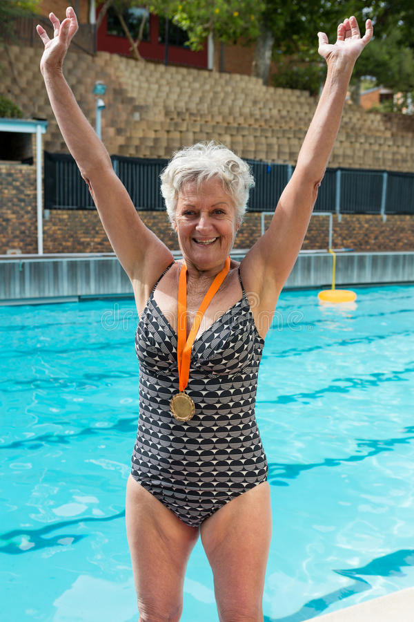 Excited senior woman with gold medals around her neck standing at poolside royalty free stock image
