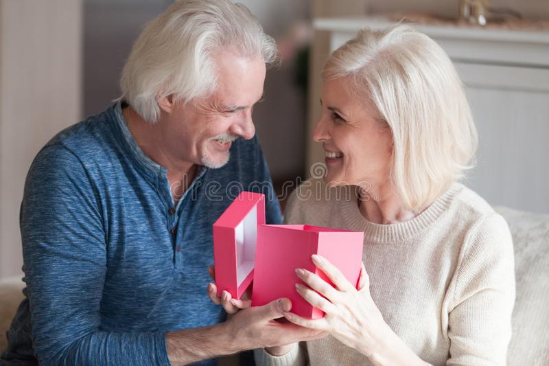 Excited senior woman opening gift box receiving present from hus stock photography