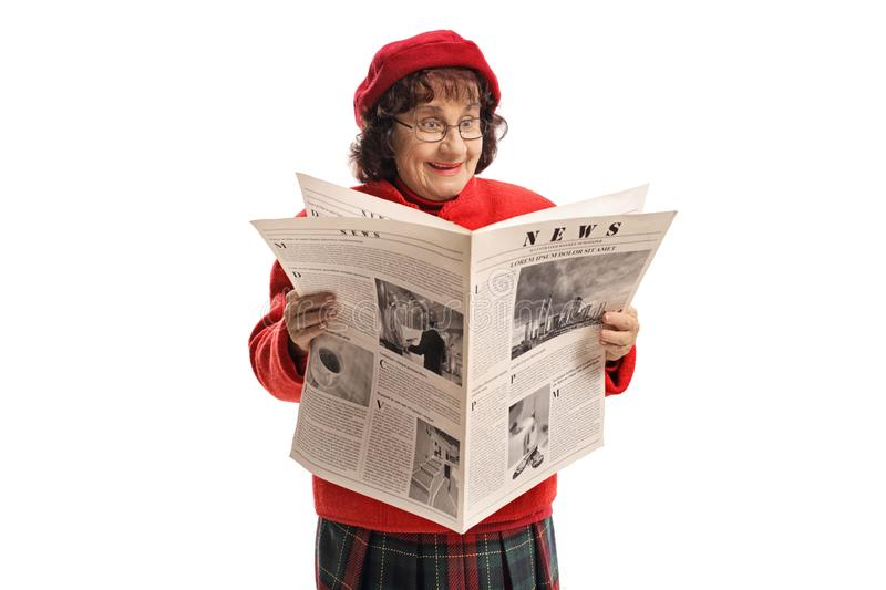 Excited senior woman with a red beret reading a newspaper royalty free stock photos
