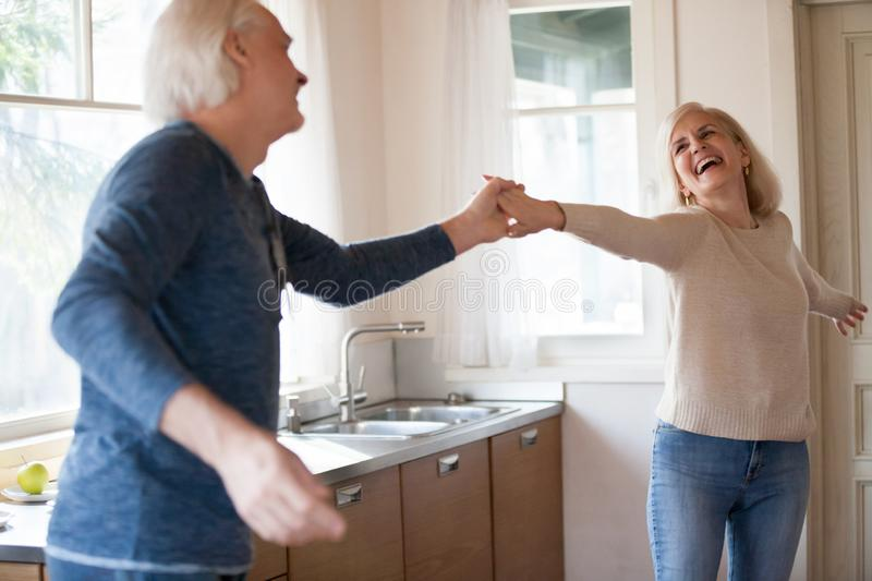 Excited happy senior woman dancing with husband in the kitchen royalty free stock images