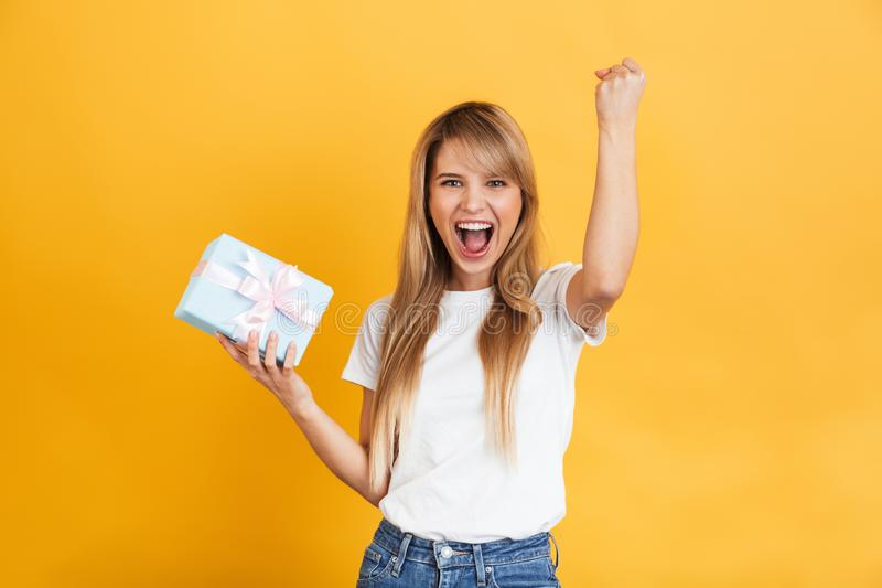 Excited shocked blonde woman posing isolated over yellow wall background holding present gift box make winner gesture royalty free stock photography