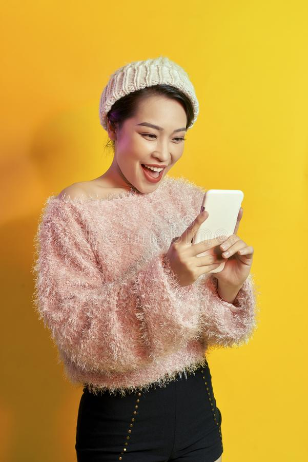 Excited short-haired woman holding smartphone on orange background. Indoor photo of wonderful female model with posing with phone royalty free stock image