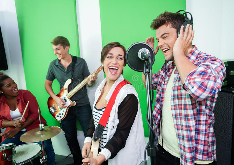 Excited Singers Performing While Colleagues Playing Musical Inst stock photo