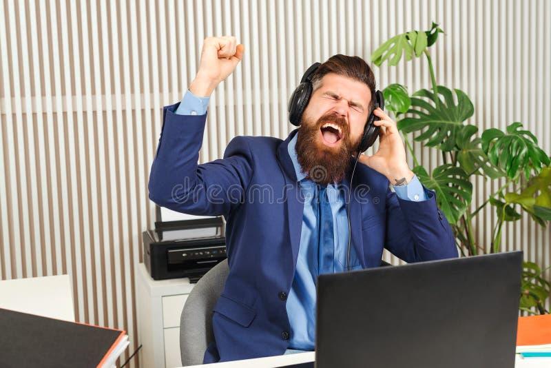 Excited skäggig affärsman i hörlurar på arbetsplatsen Lyckad man som arbetar i coworking kontor Stilig man spännande av online- royaltyfri bild