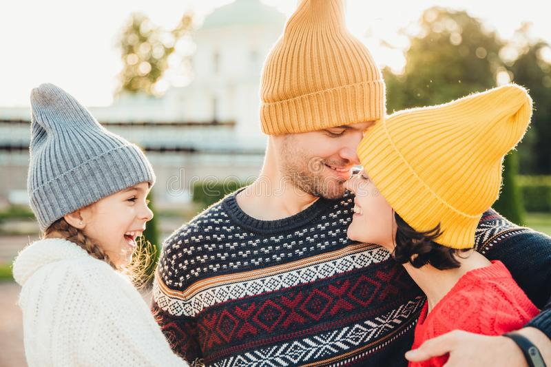 Excited small kid looks at her parents who are in love, going to kiss each other, have goos relationships, embrace. Affectionate w royalty free stock image