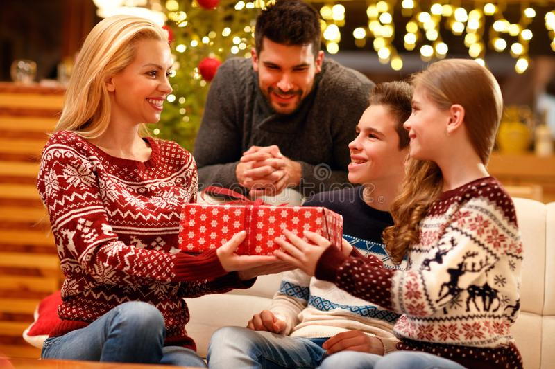 Excited daughter giving her loving mother Christmas present royalty free stock photo