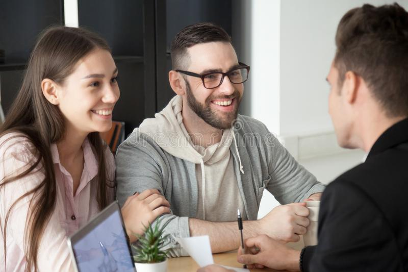 Excited smiling millennial couple discussing mortgage loan inves. Tment or real estate purchase with realtor, happy young clients customers being consulted by royalty free stock image